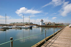 Yacht Club View. View of a yacht club with a lighthouse in the background royalty free stock image