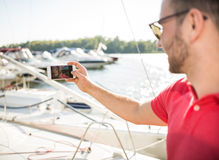 Yacht club. Young successful businessman holding time on the yacht Royalty Free Stock Photos