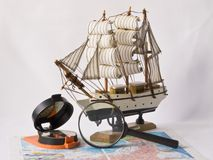 Yacht, a compass and magnifying glass on the map Stock Image