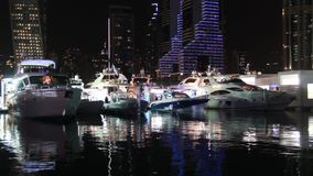Yacht de luxe accouplé à la marina de Dubaï la nuit banque de vidéos