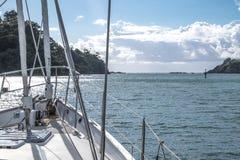 Yacht della barca a vela andando in automobile dal porto di Tutukaka fra le rocce Immagine Stock