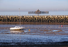 Yacht and derelict pier at low tide Stock Photos