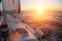 Yacht di navigazione contro il tramonto lusso Immagine Stock