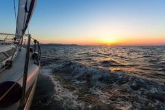 Yacht di navigazione nel mar Egeo durante la penombra Corsa Fotografie Stock