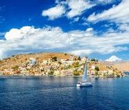 Yacht di navigazione nelle belle costruzioni dell'isola di Symi, Grecia, nuvole, cielo, giorno soleggiato luminoso Fotografie Stock Libere da Diritti