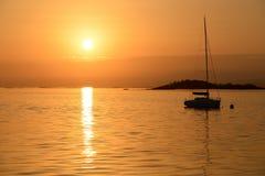Yacht di navigazione sui precedenti del tramonto Immagini Stock