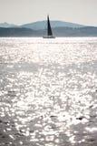 Yacht di navigazione sul mare contro il sole con le riflessioni Immagini Stock