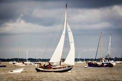 Yacht, die den Fluss unter Segel navigiert Stockfoto