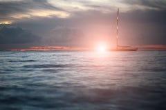 Yacht, die in Meer unter erstaunlichen Sonnenuntergang schwimmt Stockbilder