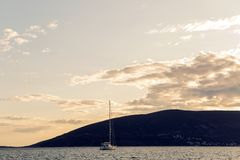 Yacht docked at the pier in the Bay of Montenegro at sunset. And mountain stock images