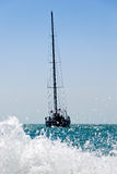 Yacht drifting in the sea. With sails down. Splash of water wave in foreground and blue sky in background Stock Photos