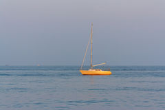 The yacht drifting in sea at sunset Royalty Free Stock Image
