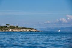 Yacht et île de navigation en mer Photographie stock