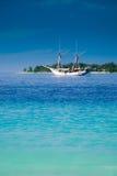 Yacht et île de tropique Image stock