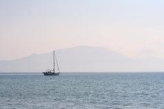 Yacht et montagne brumeuse au crépuscule Image libre de droits