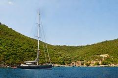 Yacht festgemacht durch Insel Lizenzfreie Stockfotografie