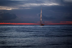 Yacht floating in sea under amazing sunset Stock Photo