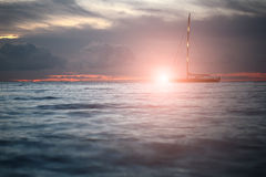 Yacht floating in sea under amazing sunset Stock Images