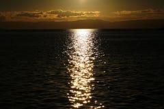 Yacht floating in sea under amazing sunset Stock Photos