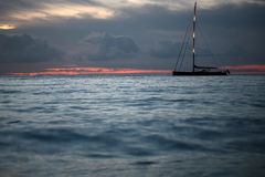 Yacht floating in sea under amazing sunset Royalty Free Stock Image