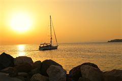 Yacht floats in the sea from marina at sunset Stock Images