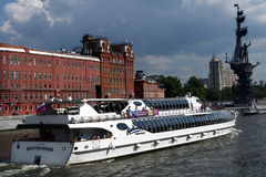 Yacht of Flotilla Radisson Royal on the Moscow river. Moscow, Russia - July 6, 2014: People traveling on the yacht of Flotilla Radisson Royal against monument to Royalty Free Stock Photos