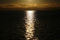 Yacht flottant en mer sous le coucher du soleil étonnant Photos stock
