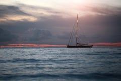 Yacht flottant en mer sous le coucher du soleil étonnant Image libre de droits