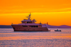 Yacht at golden sunset on open sea Stock Image