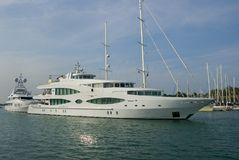 Yacht in harbor. Big white yacht in harbor with helicopter on top of rear deck stock photo