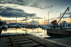 Yacht harbor, Aalborg, Denmark. The sun sets behind the yacht harbor in western Aalborg, Denmark. The tracks and crane for lowering the boats into the water in Stock Image