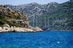The yacht in harbor among rocks and blue sea Royalty Free Stock Photos