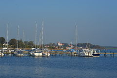 Yacht harbour in Karrebaeksminde in Denmark. Marina of Karrebaeksminde on island of Sealand, Denmark with some boats mooring and a medieval white church in the Stock Image