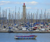 Crowded yacht harbour with lighthouse and dinghies Stock Photography