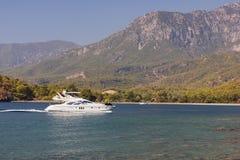 Yacht i en fjärd på bergbakgrund Fotografering för Bildbyråer