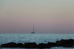 Yacht i havet på soluppgång Arkivbild