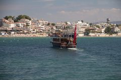 A yacht yacht iLKi3 with a group of tourists on the upper deck off the coasts popular seaside holiday resort on the Aegean coast. DIDIM, TURKEY – SEPTEMBER 6 Royalty Free Stock Image