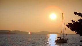 Yacht im Meer bei Sonnenuntergang auf einem Hintergrund von Bergen stock video