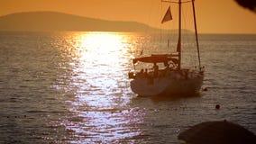Yacht im Meer bei Sonnenuntergang auf einem Hintergrund von Bergen stock footage