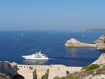 Yacht leaving Bonifacio harbor, Corsica, France. Yacht seen from the Genovese fortifications, leaving Bonifacio bay Stock Images