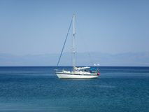 Yacht in light blue aegean sea. Yacht sailing in the aegean sea, nearby the coastline of Peloponnese Stock Images