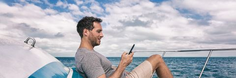 Yacht luxury lifestyle young man using cellphone banner panorama. Person relaxing on deck texting sms message on mobile phone. Under the sun summer holidays royalty free stock images