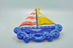 Yacht made from ceramic. Against a blue background Stock Photo