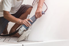 Yacht maintenance. A man polishing side of the white boat in the. Yacht maintenance. A man polishing side of the white boat by grinder machine in the marina Stock Images