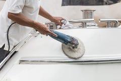 Yacht maintenance. A man polishing side of the white boat in the. Yacht maintenance. A man polishing side of the white boat by grinder machine in the marina Stock Photo
