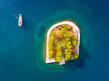 Yacht in mare vicino alla piccola isola all'entrata del porto in Vathy Ithaka Immagini Stock Libere da Diritti