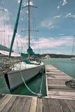 Yacht in Marina. Yacht docked at marina with blue sails on sunny day Stock Photos