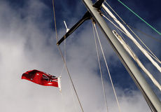 Yacht Mast Flying Flag. Cruising sailboat mast pictured against a backdrop of rich blue Australian sky and white fluffy cloud flying the Australian Red Ensign Stock Photo