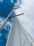 Yacht mast with the sail on the blue sky Stock Photos