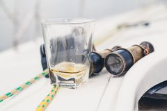 Yacht men set. glass of whiskey and an old pair of binoculars. Male set aboard the yacht. Glass with whiskey and old French binoculars close-up Royalty Free Stock Photography